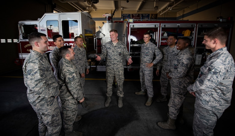 A group of Airmen talk in front of a fire truck.