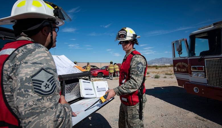 Two Air Force fire fighters review a manual.