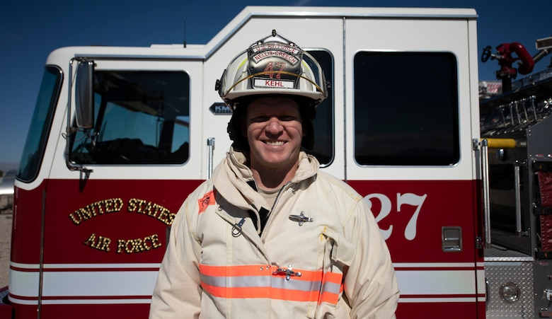An Air Force firefighter stands in front of a fire truck while wearing his gear.