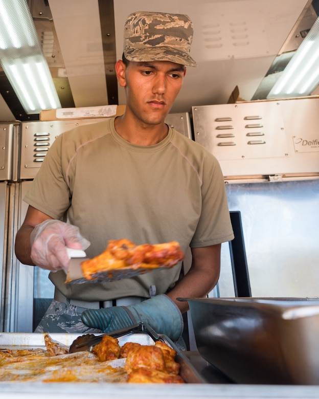 U.S. Air Force Senior Airman Ernesto Lopez Falcon, a services specialist with the 116th Air Control Wing (ACW), Georgia Air National Guard, prepares chicken wings for lunch from a Disaster Relief Mobile Kitchen Trailer during Innovative Readiness Training at Camp Paumalu Girl Scout Camp, Hawaii, July 24, 2019.