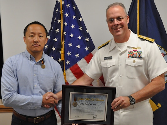 IMAGE: DAHLGREN, Va. (Aug. 30, 2019) – Naval Sea Systems Warfare Centers Commander Rear Adm. Eric Ver Hage presents the Secretary of Defense Medal for the Global War on Terrorism (GWOT) plaque to Richard Oh at an award ceremony moments after pinning GWOT Medal on Oh – a Naval Surface Warfare Center Dahlgren Division (NSWCDD) engineer. The GWOT Medal recognized and honored Oh's contributions and accomplishments in direct support of the armed forces engaged in operations to combat terrorism.