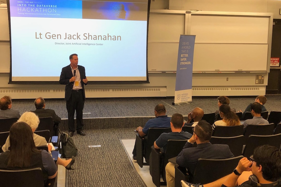 "A man holding a microphone stands in front of a projection screen that reads ""Lt. Gen. Jack Shanahan."""