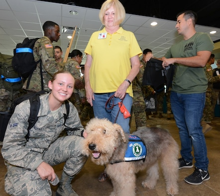 An Airman poses for a photo with a working therapy dog brought by volunteers with Paws 4 Hearts.