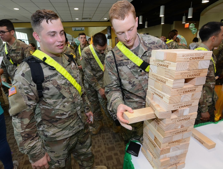 "A Soldier slowly pulls out a wooden block from a tower labeled with ""Together Working For Change."""