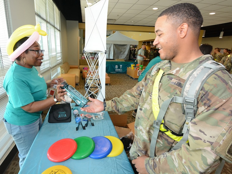 A Soldier answers a question about the Army SHARP program at the Frisbee booth.