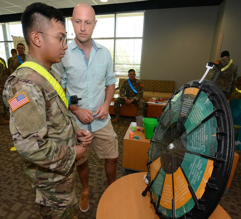 A Soldier spins the SHARP wheel that contains questions about the program.