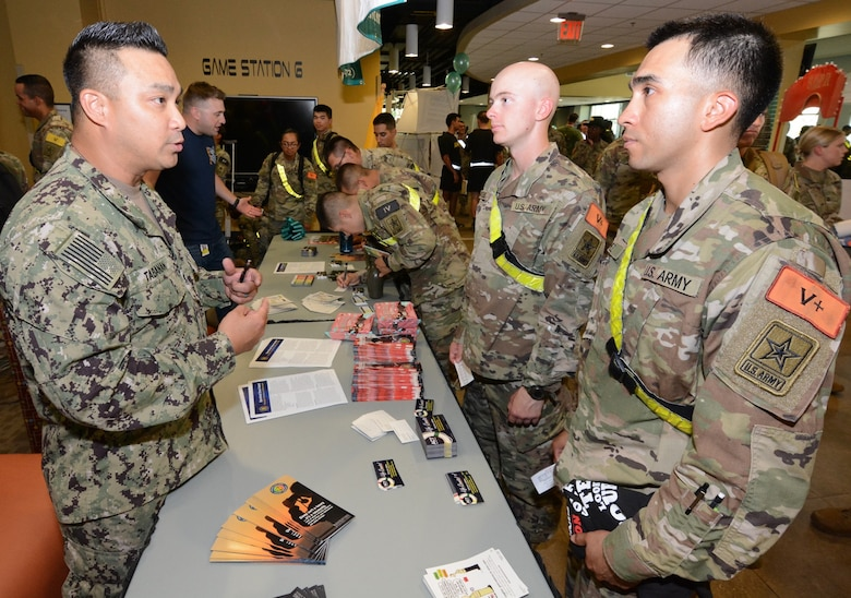 Soldiers stop by the Navy Ask, Care, and Treatment, or ACT, booth. The ACT program is a three-step process designed to help determine if someone is suicidal and to prevent them from hurting themselves.