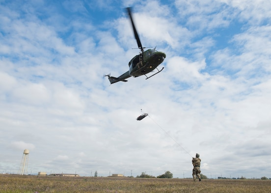 U.S. Air Force Tech. Sgt. James Pennington, 336th Training Group independent medical technician, and members from the 36th Rescue Squadron perform a rescue demonstration prior to the commemoration ceremony of the 36th RQS reaching 700 saves at Fairchild Air Force Base, Washington, Sept. 20, 2019. The 36th RQS is the only operational rescue squadron flying UH-1N helicopters within the United States that is qualified to perform 24-hour medical evacuation alert, water rescue, cargo sling and hoist operations. (U.S. Air Force photo by Airman 1st Class Lawrence Sena)