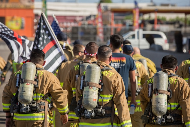 U.S. Marines with Aircraft Rescue and Firefighting (ARFF), Headquarters and Headquarters Squadron (H&HS), Marine Corps Air Station (MCAS) Yuma participate in Yuma's local 9/11 Moving Tribute 5K in Yuma, Ariz., Sept. 11, 2019. MCAS Yuma's ARFF ran alongside local fire departments, and civilians, remembering and honoring the victims of 9/11. The 5K began at City of Yuma Fire Station #3 and finished at City of Yuma Fire Station #1. (U.S. Marine Corps photo by Sgt. Allison Lotz)