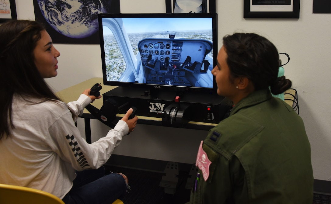 An Air Education and Training Command Women's Fly-In Event participant guides a young woman through a flight simulator at the Girls in Aviation Day