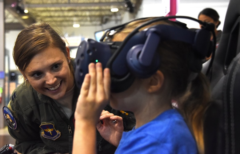 An Air Education and Training Command Women's Fly-In Event participant guides a young woman through a virtual reality