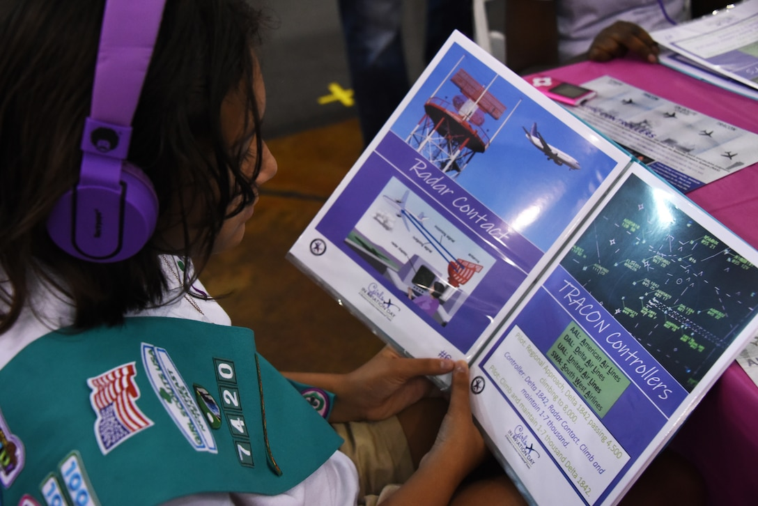 A girl scout studies a book of air traffic phraseology during the Girls in Aviation Day