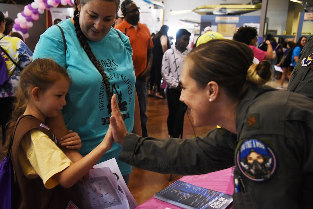 An Air Education and Training Command Women's Fly-In Event participant high-fives a young woman during the Girls in Aviation Day