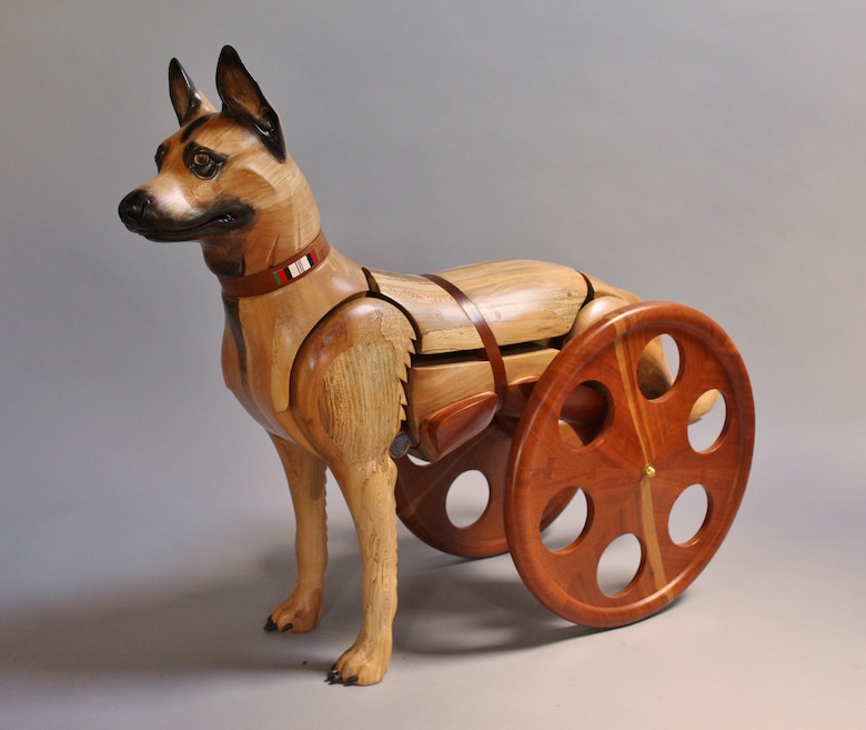 Wooden sculpture depicting a dog with its hind legs amputated and using a wheelchair.
