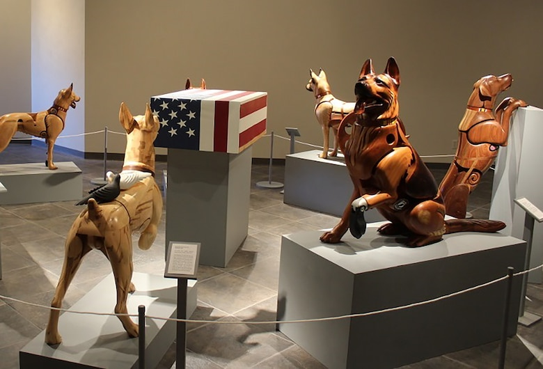 Picture showing wooden sculpture dogs on display as an exhibit.