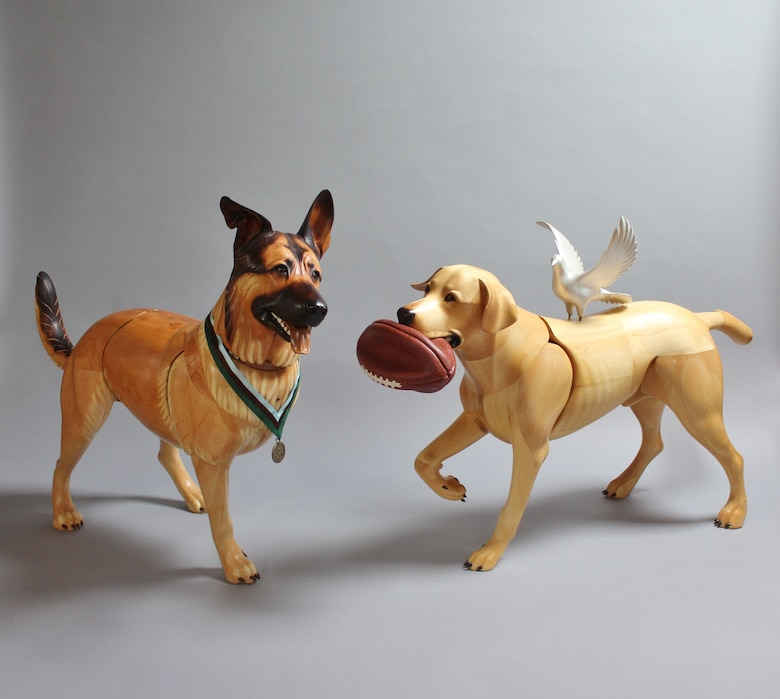 Picture of wooden sculpture dogs. The dog on the left, Lucca, has his front leg amputated and is wearing a medal around her neck. The dog on the right, Cooper, has a deflated football in her mouth and a white dove on her back.