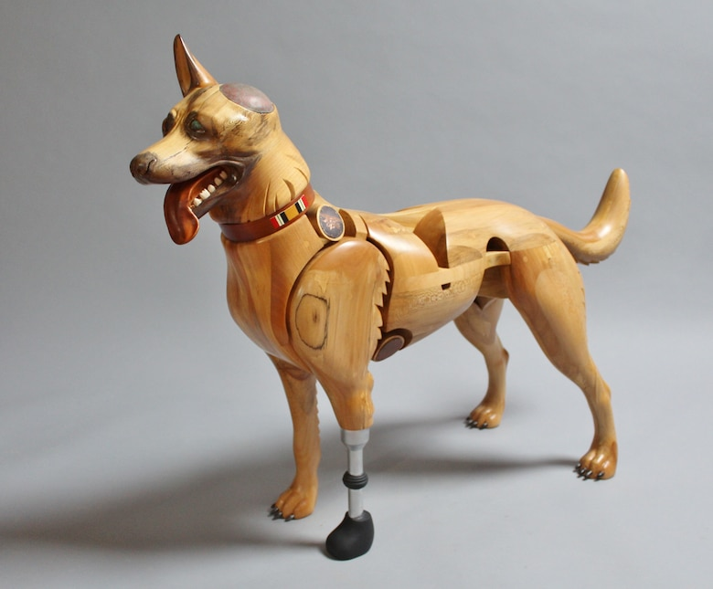 Picture of a wood sculpture dog who is missing an ear and has a prosthetic leg.
