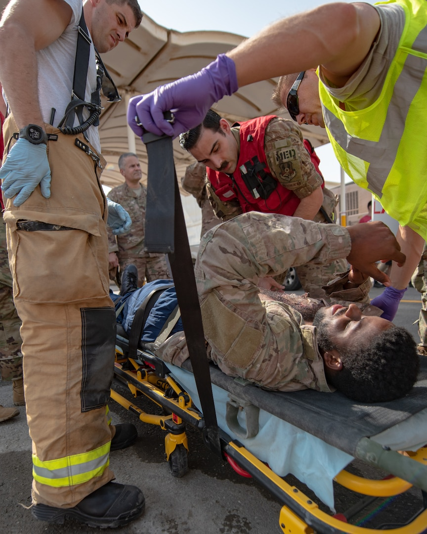 380th Air Expeditionary Wing firefighters and medics secure a moulage victim to a gurney during a large first responder exercise Sept. 24, 2019, at Al Dhafra Air Base, United Arab Emirates. A variety of agencies including medics, firefighters and security forces defenders participated in the exercise to test their readiness, knowledge of emergency procedures and interagency cooperation amongst the wing's first responders. (U.S. Air Force photo by Staff Sgt. Chris Thornbury)