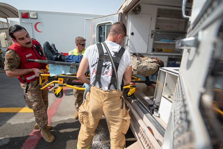 380th Air Expeditionary Wing firefighters and medics move a moulage victim into an ambulance during a large first responder exercise Sept. 24, 2019, at Al Dhafra Air Base, United Arab Emirates. A variety of agencies including medics, firefighters and security forces defenders participated in the exercise to test their readiness, knowledge of emergency procedures and interagency cooperation amongst the wing's first responders. (U.S. Air Force photo by Staff Sgt. Chris Thornbury)