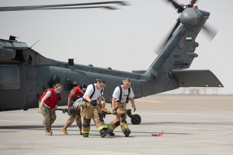 380th Air Expeditionary Wing firefighters and medics remove a simulated patient from an Emirati UH-60 Black Hawk during a large first responder exercise Sept. 24, 2019, at Al Dhafra Air Base, United Arab Emirates. The exercise helped foster partnership with the United Arab Emirates Air Force Joint Aviation Command to practice an aeromedical evacuation scenario via helicopter. (U.S. Air Force photo by Staff Sgt. Chris Thornbury)
