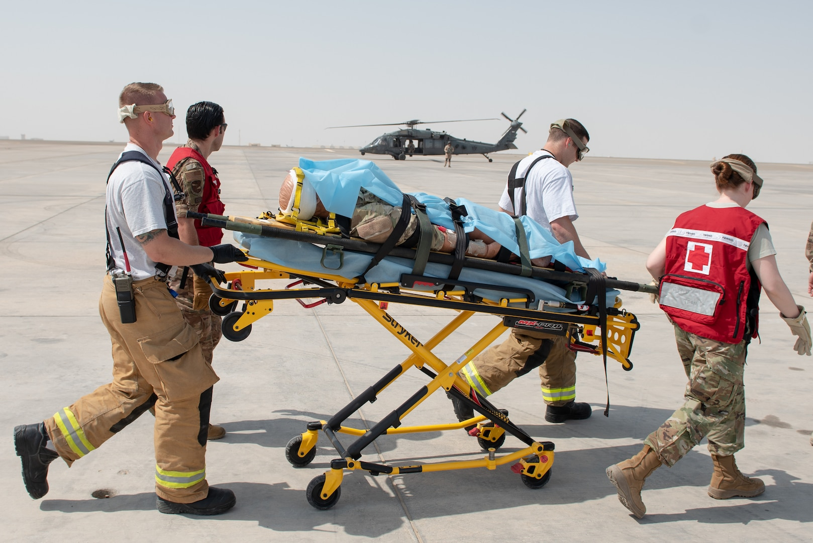 380th Air Expeditionary Wing firefighters and medics move a simulated patient to an Emirati UH-60 Black Hawk during a large first responder exercise Sept. 24, 2019, at Al Dhafra Air Base, United Arab Emirates. The exercise helped foster partnership with the United Arab Emirates Air Force Joint Aviation Command to practice an aeromedical evacuation scenario via helicopter. (U.S. Air Force photo by Staff Sgt. Chris Thornbury)