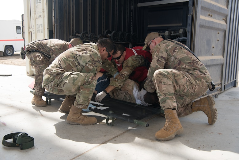 First responders work together to roll a simulated casualty onto a litter during a first responder exercise Sept. 24, 2019, on Al Dhafra Air Base, United Arab Emirates. A variety of agencies including medics, firefighters and security forces defenders participated in the exercise to test their readiness, knowledge of emergency procedures and interagency cooperation amongst the wing's first responders. (U.S. Air Force photo by Tech. Sgt. Jocelyn A. Ford)