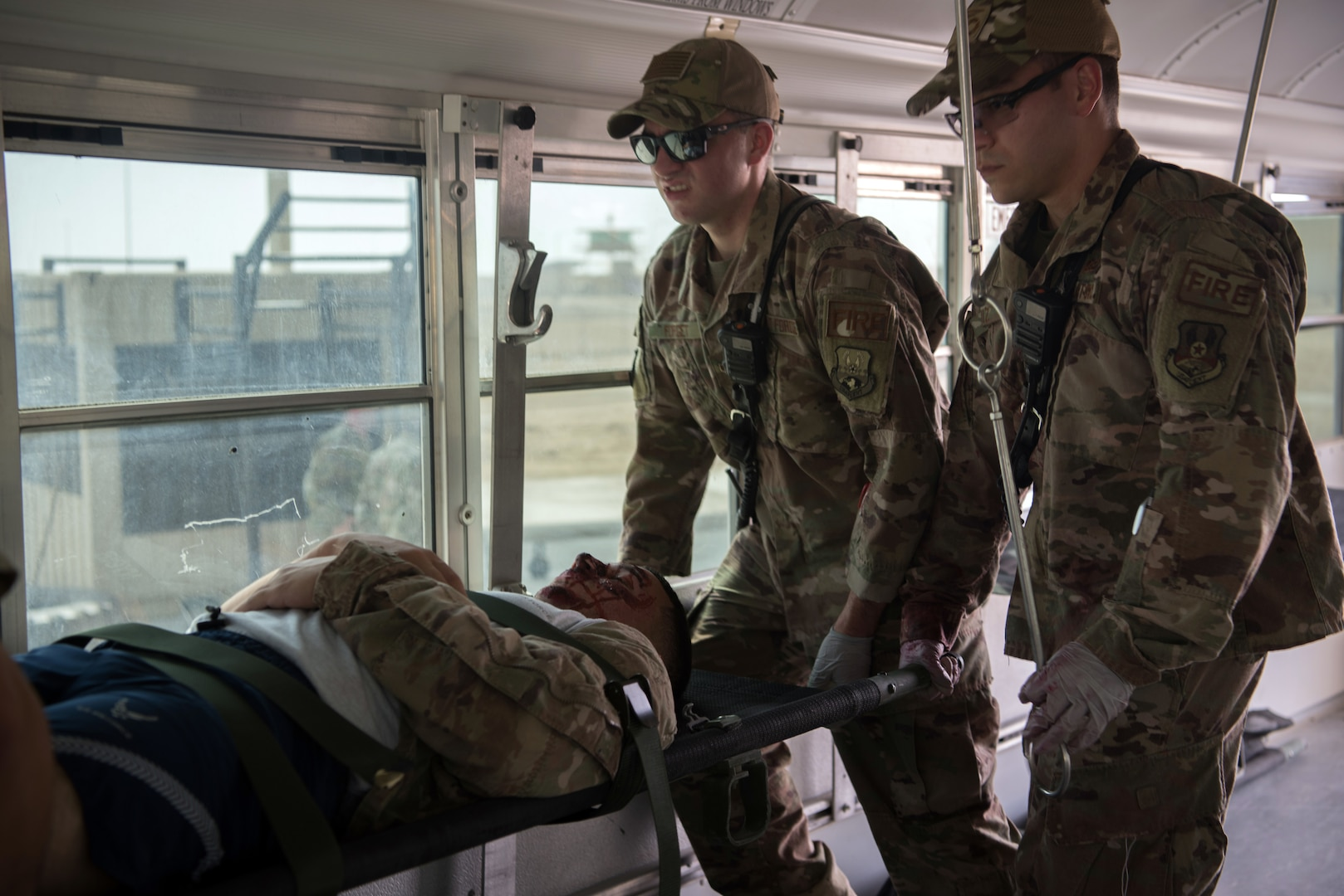 Firefighters assigned to the 380th Expeditionary Civil Engineer Squadron load a simulated casualty onto a medical transportation bus during a first responder exercise Sept. 24, 2019, on Al Dhafra Air Base, United Arab Emirates. The exercise showcased the readiness, knowledge of emergency procedures and interagency cooperation amongst the wing's first responders. (U.S. Air Force photo by Tech. Sgt. Jocelyn A. Ford)