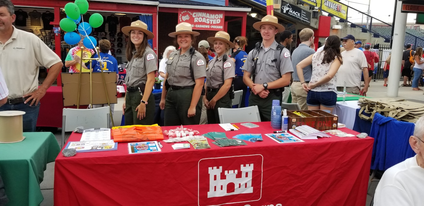 Four Park Rangers pose at an exhibit table with water safety materials during an event.