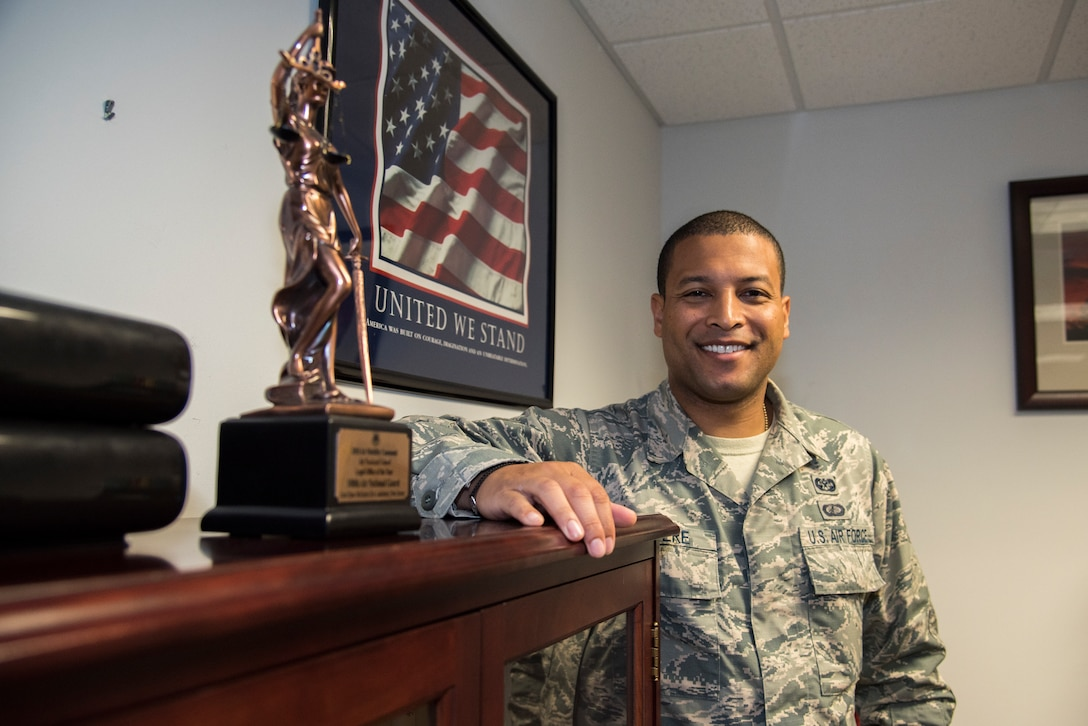 """Senior Airman Louis Chevere, a 108th Wing paralegal, stands in the wing's legal office at Joint Base McGuire-Dix-Lakehurst, N.J., Sept. 24, 2019. Chevere joined the Air National Guard seven years ago to serve his country and for better education and career opportunities. """"My favorite part of Puerto Rican culture is the food and music,"""" said Chevere. """"Nothing else compares to it."""""""