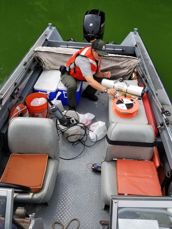 A Park Ranger riding on a boat collects a water sample for testing and monitoring purposes.
