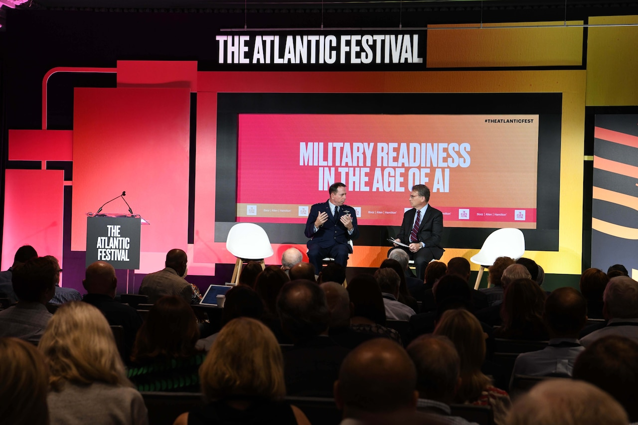 "View from audience of two men on a stage talking. Above them, signs read, ""The Atlantic Festival"" and ""Military Readiness in the Age of AI."""