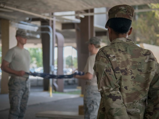 Airman First Class Jordyn Young, 35th Intelligence Squadron cyber threat analyst, trains two Joint Base San Antonio Honor Guard trainees Sept. 9, 2019 at the JBSA Honor Guard Squadron. JBSA Honor Guard trainers are guardsmen currently in honor guard duty who are chosen to teach others because of their exceptional performance in honor guard.