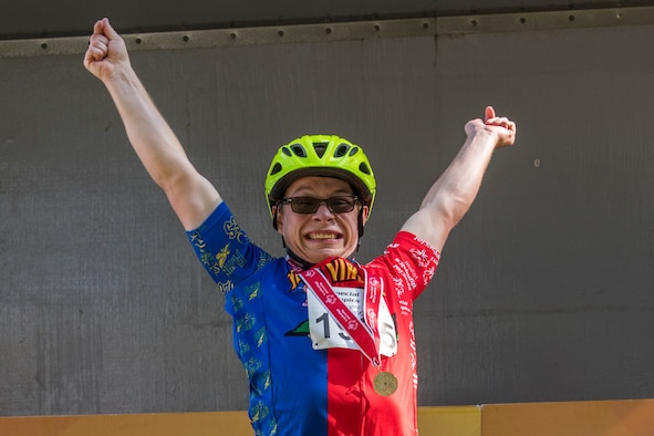Will Dickson, a contestant, raises his hands up high after receiving a gold medal during the Special Olympics 2019 cycling tournament Sept. 21, 2019, at Dover Air Force Base, Del. The contestants were awarded medals after each race, based on their divisions. (U.S. Air Force photo by Senior Airman Christopher Quail)