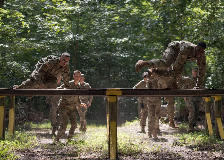 U.S. Army initial entry training Soldiers jump over hurdles during a field training exercise at Joint Base Langley-Eustis, Virginia, Sept. 18, 2019.