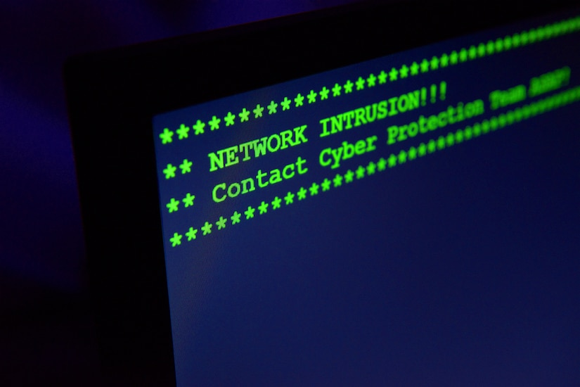 "In a dark room, the words ""NETWORK INTRUSION!!! Contact Cyber Protection Team ASAP"" flash on a computer screen."