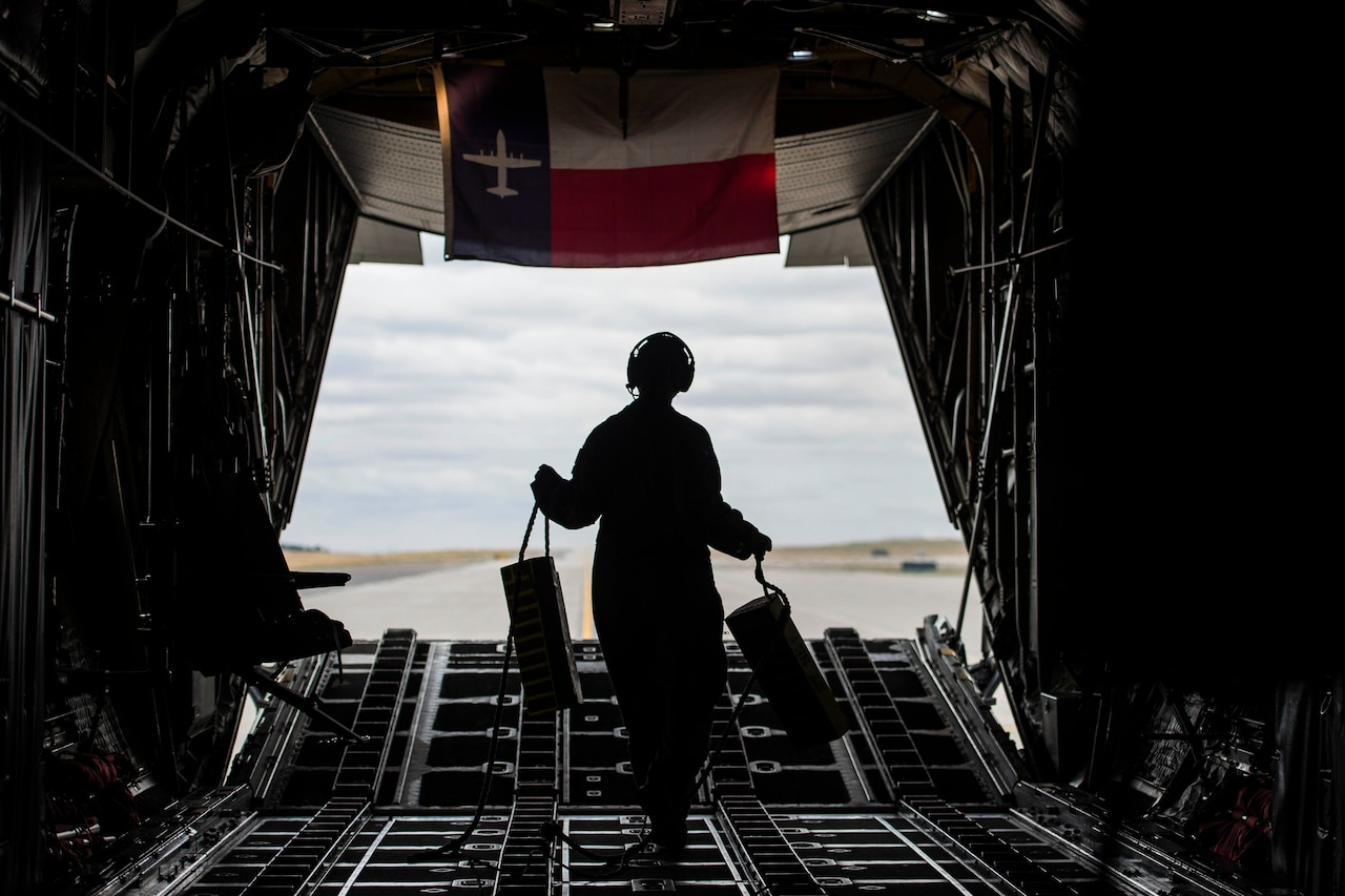 An airman walks inside an aircraft holding two blocks.