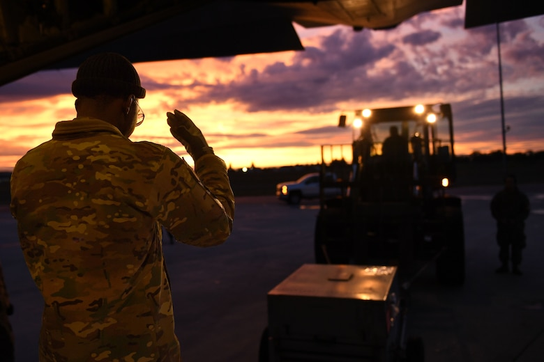 A man marshalls a vehicle.