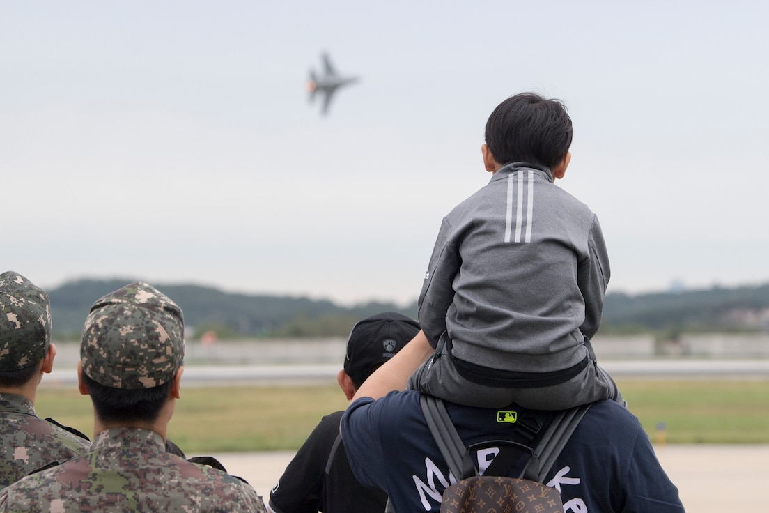 A child and his father watch the Pacific Air Force's F-16 Viper Demonstration Team perform during Osan's Air Power Day Sept. 21, 2019, at Osan Air Base, Republic of Korea. The event celebrates the US-ROK alliance and features aerial performances, static displays and a multitude of festivities. (U.S. Air Force photo by Staff Sgt. Ramon A. Adelan)