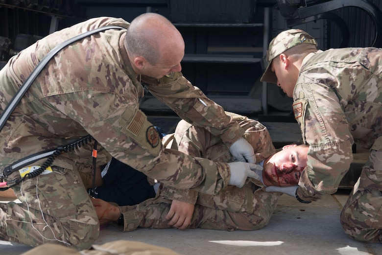 Firefighters assigned to the 380th Expeditionary Civil Engineer Squadron medically evaluate Senior Airman Naseem Eissa, 380th Expeditionary Logistics Readiness Squadron ground transportation operator, a moulage victim, during an exercise on Al Dhafra Air Base, United Arab Emirates, Sept. 24, 2019. A variety of agencies including medics, firefighters and security forces defenders participated in the exercise to test their readiness, knowledge of emergency procedures and interagency cooperation amongst the wing's first responders. (U.S. Air Force photo by Tech. Sgt. Jocelyn A. Ford)