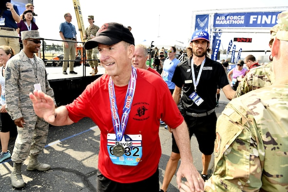 Air Force Chief of Staff Gen. David L. Goldfein acknowledges congratulations after finishing the Air Force Half Marathon Sept. 21, 2019 at Wright-Patterson AFB, Ohio. Goldfein's shirt honored the Special Tactics Memorial March earlier this year that paid tribute to Staff Sgt. Dylan Elchin a Special Tactics combat controller who was killed in Afghanistan in 2018. His hat carried a SERE instructor logo that was given to him during a visit to Fairchild AFB. (U.S. Air Force photo by Scott Ash)