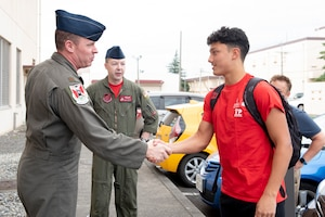 Maj. Frank Zientek, 36th Airlift Squadron chief pilot, greets Joey DeGrella, Yokota High School senior and Junior Reserve Officer Training Corps. class commander, prior to making DeGrella an honorary the Pilot for a Day, Sept. 20, 2019, at Yokota Air Base, Japan