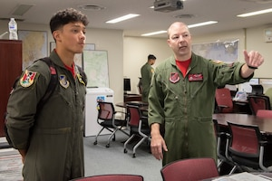 Joey DeGrella, Yokota High School senior and Junior Reserve Officer Training Corps. class commander, learns how each office contributes to the overall mission of the 36th Airlift Squadron from Master Sgt. Michael McArty, 36 AS C-130J Super Hercules instructor loadmaster, during the Pilot for a Day program, Sept. 20, 2019, at Yokota Air Base, Japan.