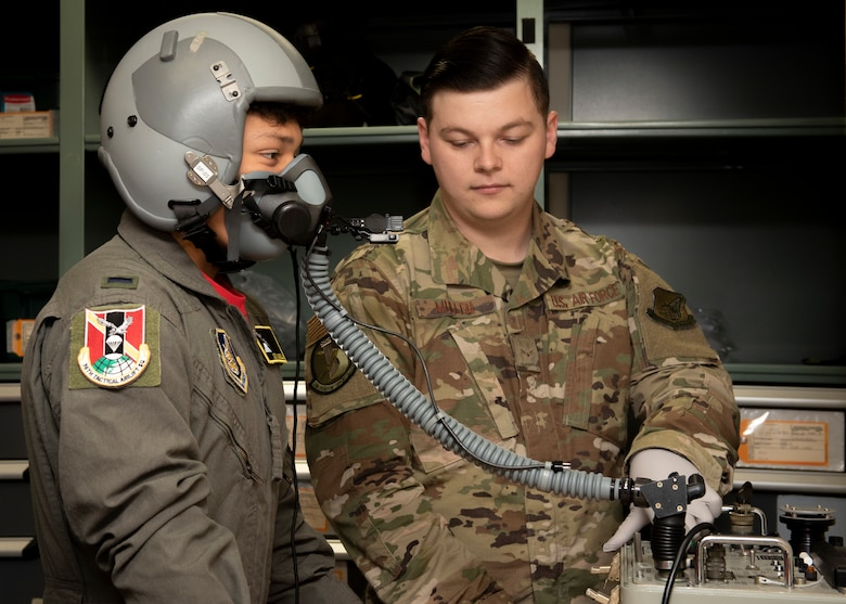 Joey DeGrella, 36th Airlift Squadron pilot for a day program participant, tries on an oxygen mask in the aircrew flight equipment office at Yokota Air Base, Japan, Sept. 20, 2019