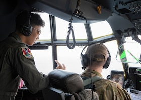 Capt. Sean Boyington, 36th Airlift Squadron C-130J Super Hercules instructor pilot, talks to Joey DeGrella, Pilot for a Day participant, while flying over the Pacific Ocean of the eastern coast of Japan, Sept. 20, 2019.