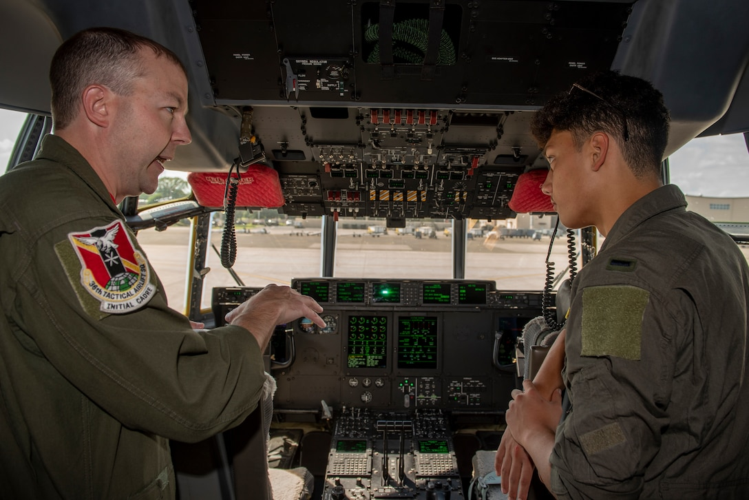 Master Sgt. Michael McArty, 36th Airlift Squadron C-130J Super Hercules instructor loadmaster, explains the controls of a C-130J Super Hercules cockpit to Joey DeGrella, Yokota High School senior and Junior Reserve Officer Training Corps. class commander, who was selected as the Pilot for a Day program, Sept. 20, 2019, at Yokota Air Base, Japan.