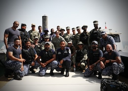 U.S. Navy Sailors assigned to Task Force Shore Battle Space and members of the Bahraini Coast Guard pose for a photo after training during exercise Neon Defender 19. Exercise Neon Defender 19 is a bilateral surface and maritime security exercise between the U.S. Navy and Bahrain Defense Force to enhance interoperability and war fighting readiness, fortify military- to- military relationships between the United States and the Kingdom of Bahrain, advance mutual operational capabilities and strengthen civil-to-military relationships.