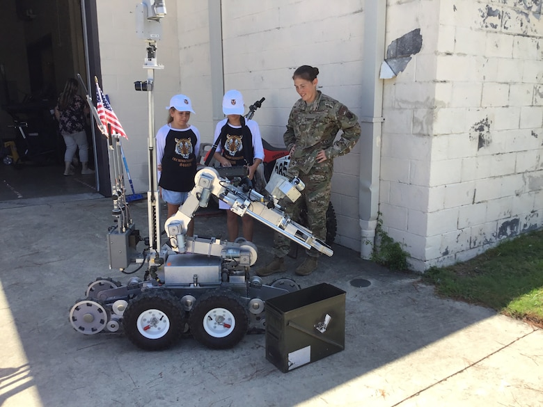 Tech. Sgt. Jacqueline Risby teaches Kaitlyn Nolte and Sloan Mann how to operate an F6 Andros EOD robot.