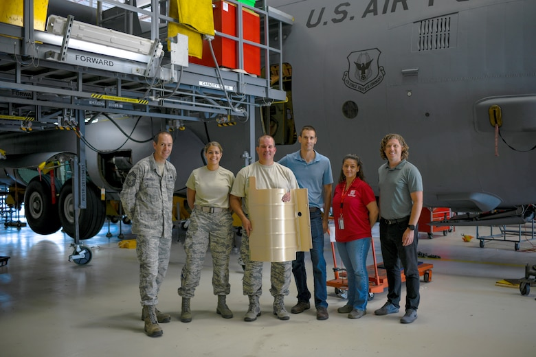 Reservists pose with the first AAM piece to be fitted on a C-130H.