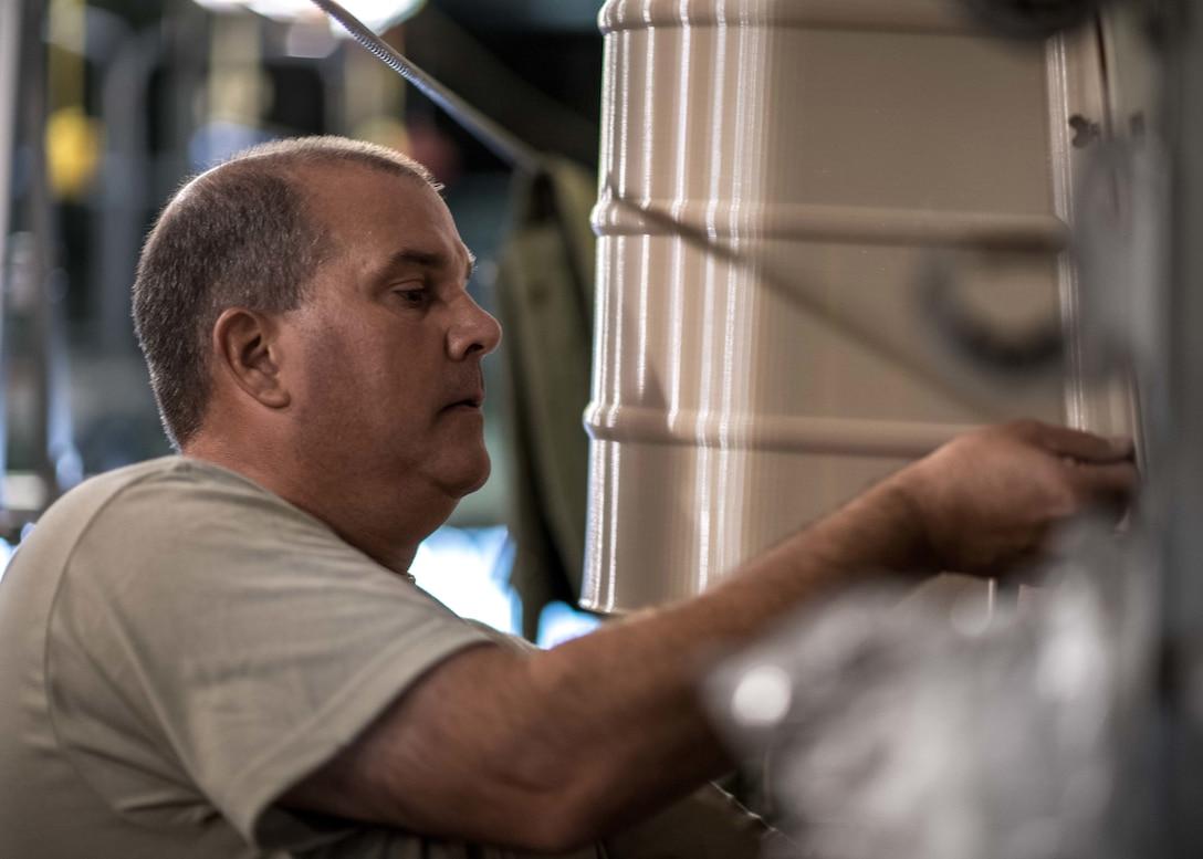 Master Sgt. Scott Obermiyer installs the first Advanced Additive Manufacturing piece.