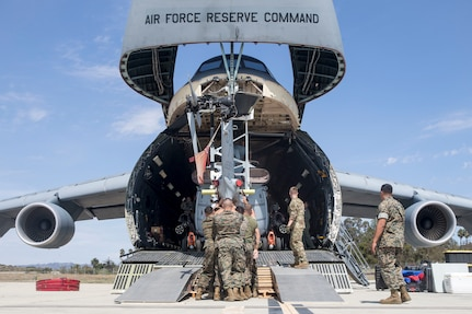 U.S. Marines and Airmen assist in loading a UH-1Y Venom into C-5M Super Galaxy at Marine Corps Air Station Camp Pendleton, California, Sept. 16. The C-5M was a visiting U.S. Air Force aircraft from 433rd Airlift Wing at Joint Base San Antonio-Lackland, Texas, and was here as part of a dual service training exercise.